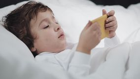 有摩擦她的眼睛的片剂的男婴在哭泣以后 他在床上在他的手上说谎,拿着一个黄色智能手机 影视素材