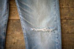 有撕毁的老蓝色牛仔裤在木背景 免版税库存图片