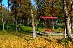 有操场摇摆集合和供徒步旅行的小道的充满活力的秋天森林 图库摄影
