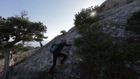 有攀登和到达山的上面的小背包的年轻女人 山顶的夫人在吻合风景 股票录像