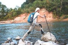 有攀登石头的蓝色背包的远足者 免版税库存图片