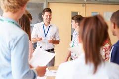 有支持书桌的大学生的老师在教室 免版税库存照片