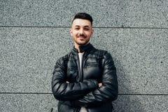 有支持墙壁的背包的阿拉伯学生外面 年轻行家人等待的groupmates 图库摄影