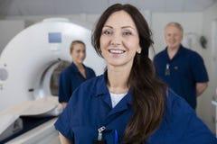 有支持MRI Machi的同事的微笑的女性放射学家 免版税库存照片