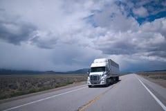 有收帆水手拖车的半卡车在平的长的亚利桑那路 免版税库存图片