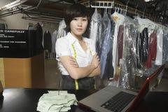 有收据钉的确信的在柜台的妇女和膝上型计算机在洗衣店 免版税库存图片
