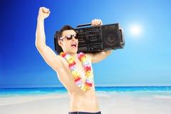 有收音机的愉快的人在他的肩膀打手势幸福的在旁边 免版税库存照片