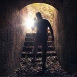 有收音机的年轻人出去黑暗的石隧道 免版税库存照片