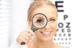 有放大器和视力检查表的妇女 图库摄影