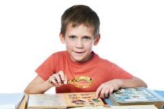 有放大器的男孩看他的被隔绝的集邮 免版税库存照片