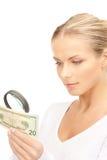 有放大镜和金钱的妇女 免版税库存图片