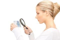 有放大镜和金钱的妇女 免版税库存照片
