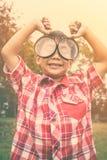 有放大镜的亚裔男孩在公园在度假 温暖的口气 免版税库存图片