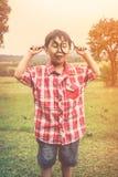 有放大镜的亚裔男孩在公园在度假 温暖的口气 免版税图库摄影