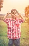 有放大镜的亚裔男孩在公园在度假 温暖的口气 库存图片