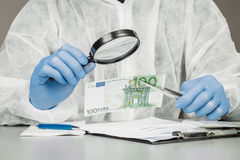 有放大镜的人检查可疑金钱 库存图片