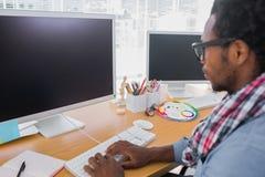 有放大镜的企业工作者在计算机上 免版税库存照片