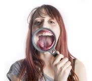 有放大镜的妇女在开放嘴前面 免版税库存图片