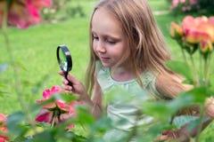 有放大镜的小女孩在庭院里 免版税库存图片