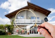 有放大镜的手在房子 免版税库存图片