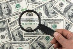 有放大镜的现有量在货币背景  免版税库存照片