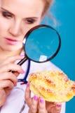 有放大镜的医生审查甜食物的 免版税库存照片