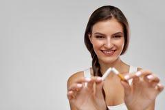 有放弃残破的香烟的美丽的愉快的女性抽烟 免版税库存图片