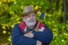 有放松在一个秋季森林里的曼陀林的资深音乐家 库存照片