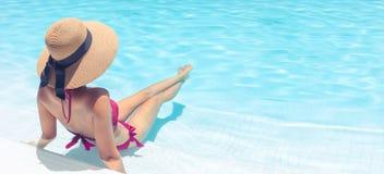 有放松在与大海的游泳池的棕色帽子的妇女在太阳,假日概念 免版税库存照片