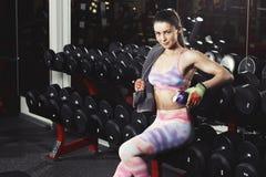 有放松在健身房的毛巾和振动器的健身女孩 免版税库存照片
