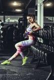 有放松在健身房的毛巾和振动器的健身女孩 库存照片