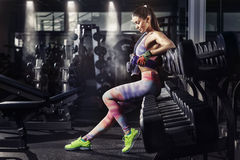 有放松在健身房的毛巾和振动器的健身女孩 免版税库存图片