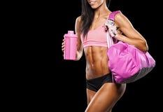 有放松在健身房的毛巾和振动器的健身女孩 库存图片
