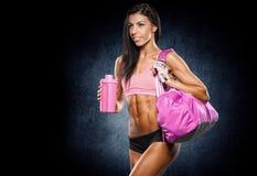 有放松在健身房的毛巾和振动器的健身女孩 图库摄影
