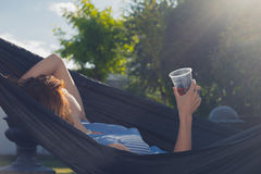 有放松在吊床的饮料的少妇 免版税库存照片