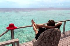 有放松在大阳台和享受在一个热带目的地的红色帽子的年轻女人自由 库存图片