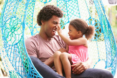 有放松在室外庭院摇摆位子的女儿的父亲 库存照片
