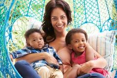 有放松在室外庭院摇摆位子的孩子的母亲 免版税库存图片