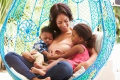 有放松在室外庭院摇摆位子的孩子的母亲 免版税库存照片