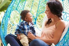 有放松在室外庭院摇摆位子的小儿子的母亲 免版税库存照片