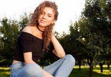 有放松在庭院里的长的头发的美丽的年轻深色的妇女在一个温暖的夏天晚上 温暖的颜色 库存图片