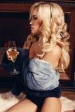 有放松在有杯的一个烟囱旁边的金发的性感的女孩香槟 库存照片