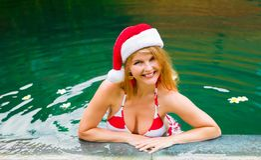 有放松在水池的红色圣诞老人帽子的妇女 免版税库存图片