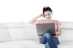 有放松在沙发的膝上型计算机的妇女 免版税库存图片