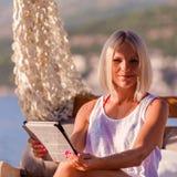 有放松在海滩的片剂的性感的白肤金发的妇女 库存图片