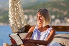 有放松在海滩的片剂的性感的白肤金发的妇女 免版税库存图片