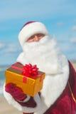 有放松在海滩的许多金黄礼物的圣诞老人 图库摄影