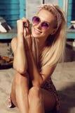 有放松在海滩的金发的华美的妇女 免版税库存照片