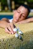 有放松在温泉极可意浴缸水池的花的妇女 免版税库存图片