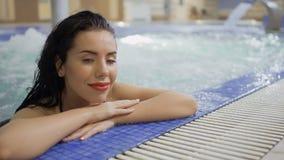 有放松在游泳池的红色嘴唇的迷人的浅黑肤色的男人 影视素材